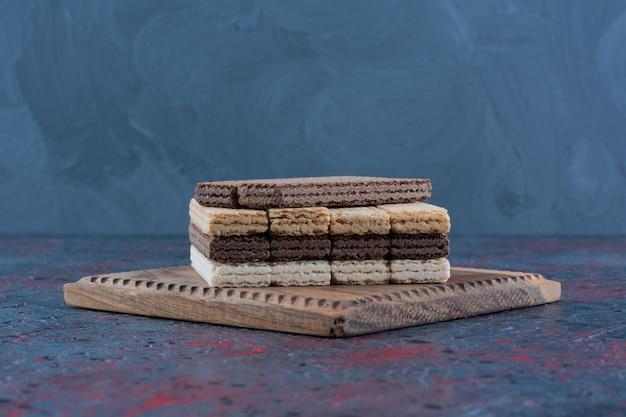 Palitos de waffle de chocolate colocados sobre um fundo escuro.