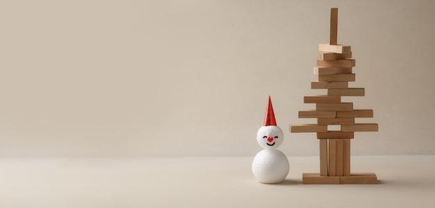 Palitos empilhados em forma de árvore de natal com boneco de neve. conceito de natal