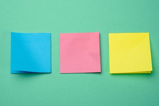 Palitos quadrados multicoloridos são colados ao fundo verde, copie o espaço