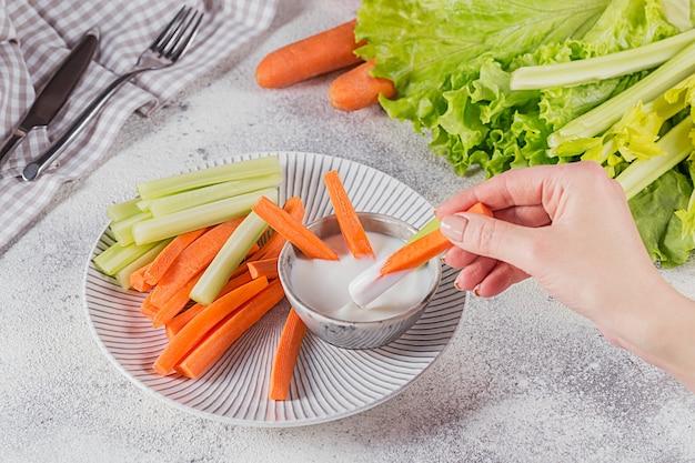 Palitos vegetais. aipo fresco e cenoura com molho de iogurte. mão de uma mulher segurando a vara de cenoura. conceito de comida saudável e dieta.