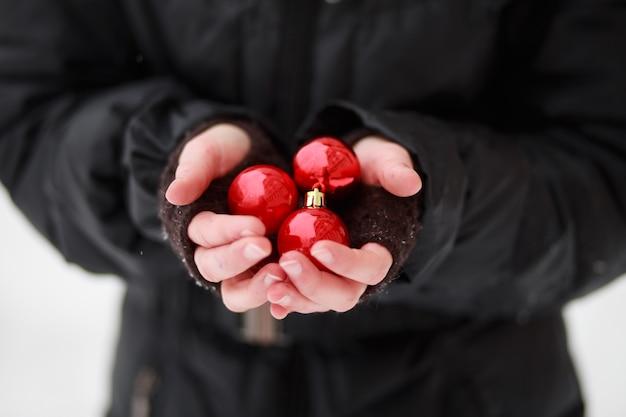 Palma congelada da criança em pé no frio e segurando três bolas vermelhas