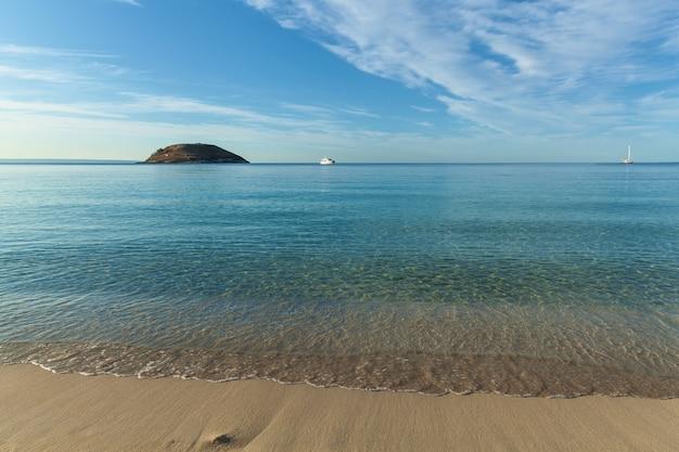 Palma de maiorca, espanha, uma praia com vista para o oceano à distância, estão dois iates
