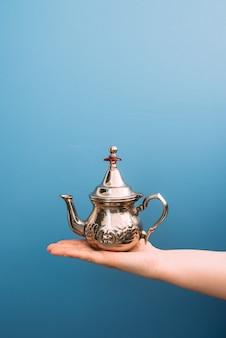 Palma de uma mulher branca segurando um bule de chá de metal sobre um fundo azul