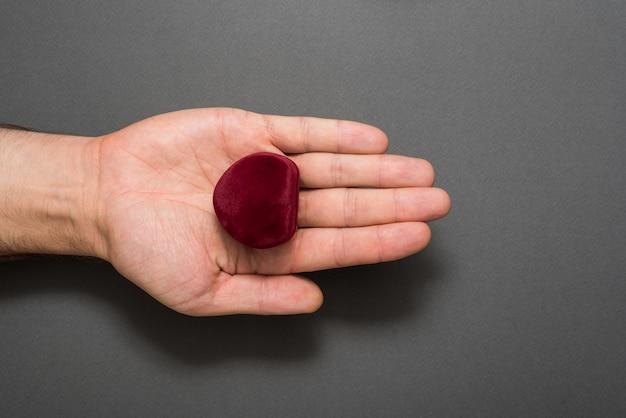 Palma masculina aberta com uma caixa de jóias vermelha em forma de coração. presente. fundo preto