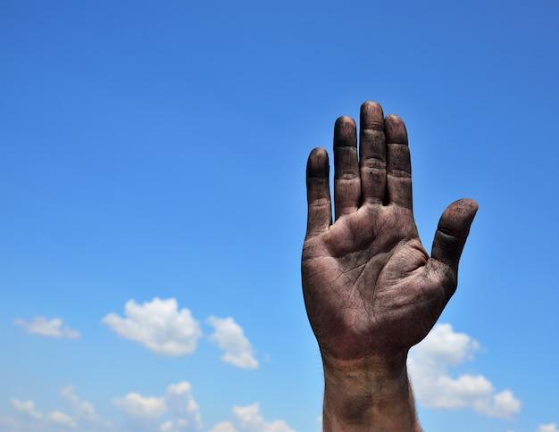 Palma masculina suja levantada contra um céu azul