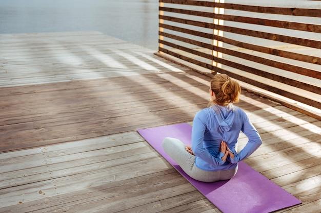Palmas dobradas. a mulher se concentrou em fazer ioga matinal, sentada no tapete de ioga