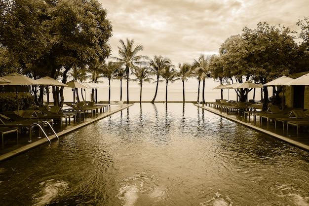 Palmeira silhueta na praia com piscina