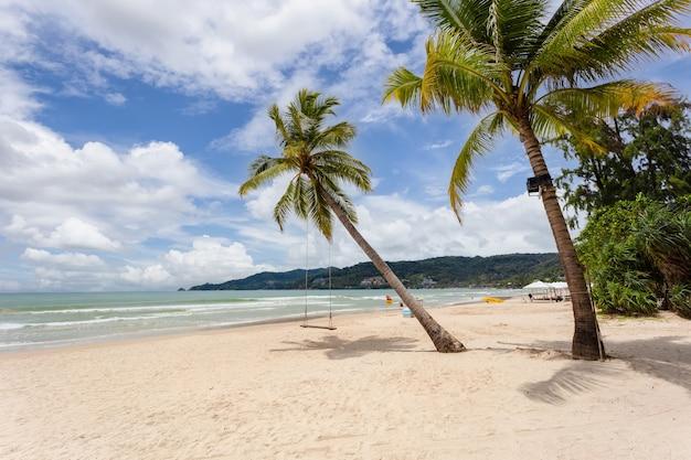 Palmeiras em uma praia com lindas areias e nuvens na paisagem de céu azul