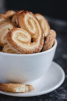 Palmier puff pastelaria. deliciosos biscoitos palmier francês com açúcar em uma tigela branca na superfície escura
