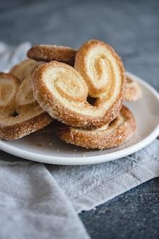 Palmier puff pastelaria. deliciosos biscoitos palmier francês com açúcar num prato branco na superfície escura
