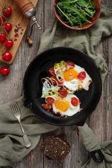 Pan com ovos fritos e tomate cereja na mesa rústica.