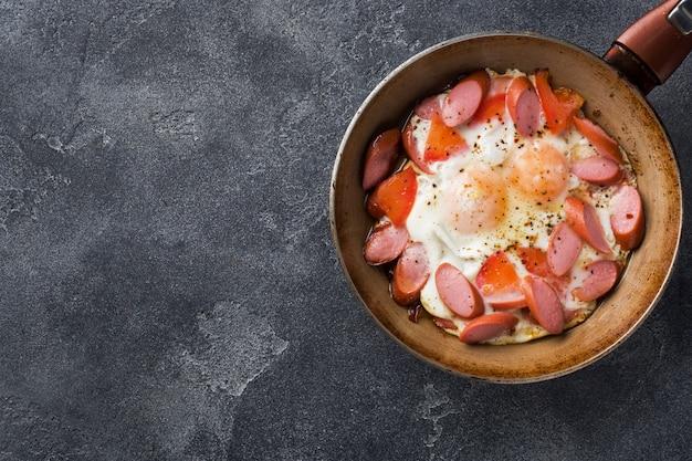 Pan com ovos fritos salsichas e tomates em cima da mesa.