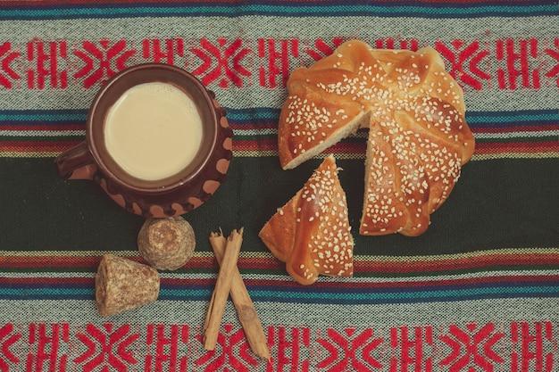 Pan de muerto y taza de chocolate sobre una mesa com manto tipico mexicano