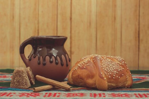 Pan de muerto y taza de chocolate sobre una mesa com manto tpico mexicano