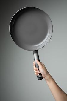 Pan-frite com a mão na cozinha de utensílio de fundo cinza para cozinhar