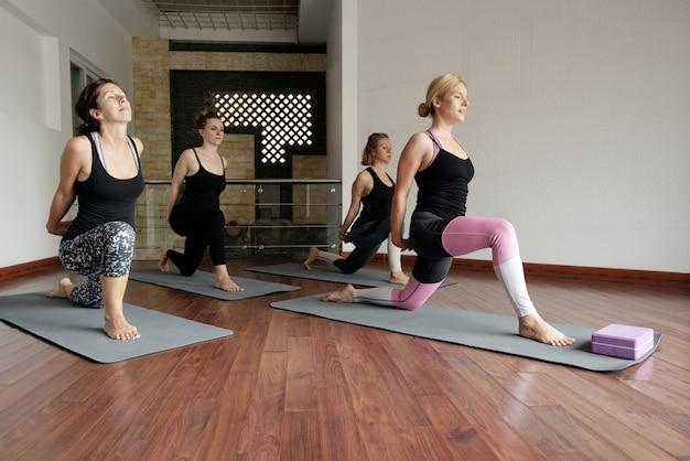 Pan vista da aula de fitness cheia de mulheres fazendo yoga