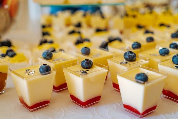 Panacottas doces com um sabor de creme e morangos e com uma baga azul estão sobre a mesa no café