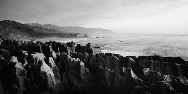 Panaroma de rochas de panqueca na vista panorâmica das montanhas, praia e pôr do sol.