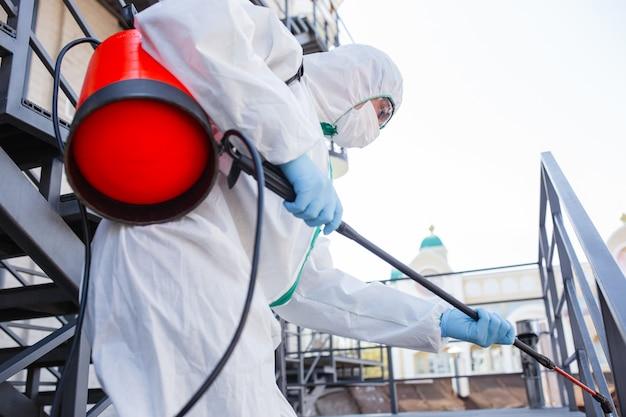 Pandemia de coronavírus. um desinfetante em traje de proteção e máscara pulveriza desinfetantes na sala.