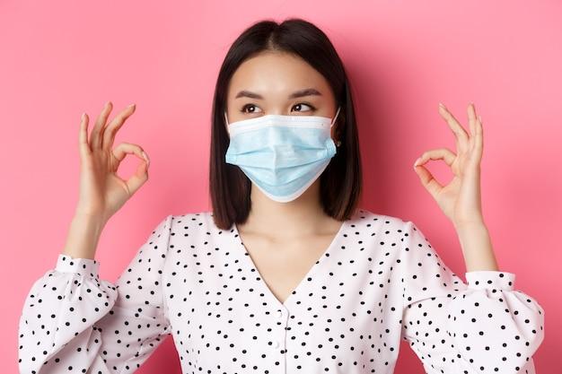Pandemia de covid e conceito de estilo de vida mulher asiática kawaii apontando os dedos para a máscara facial mostrando ok ...
