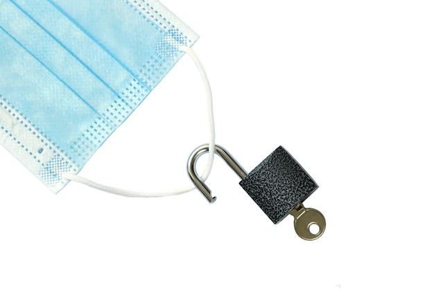 Pandemia desativada máscara médica com um cadeado desbloqueado isolado no fundo branco vista superior