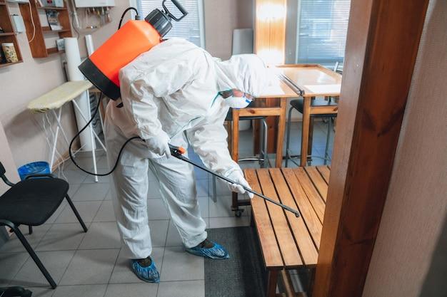 Pandemia do coronavírus. desinfetante em traje de proteção e máscara pulveriza desinfetantes em casa ou no escritório