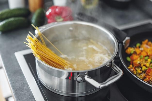Panela a ferver com cozinhar macarrão espaguete na cozinha. fechar-se
