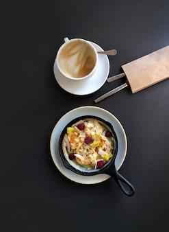 Panela com cheesecake ou panqueca e frutas vermelhas, xícara de café na mesa escura, vista superior.