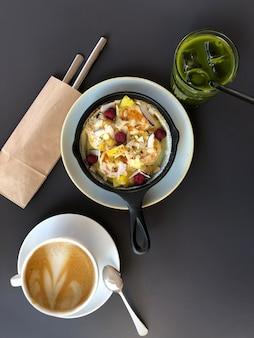 Panela com cheesecake ou panqueca e frutas, xícara de café e matcha na mesa escura, vista de cima.
