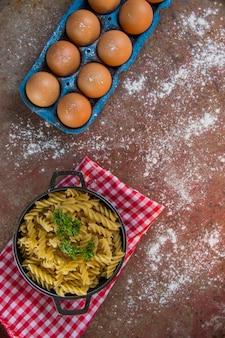 Panela com macarrão em parafusos não cozidos, acompanhada de balde de ovos, farinha e salsa