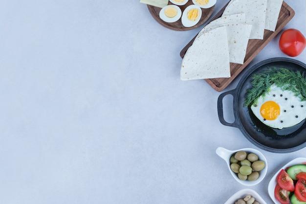 Panela com omelete e ovos cozidos, queijo, tomate, cogumelos em branco.
