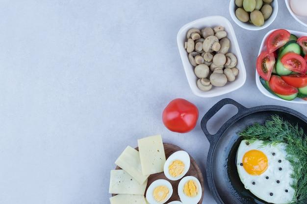Panela com omelete e ovos cozidos, queijo, tomate, cogumelos.