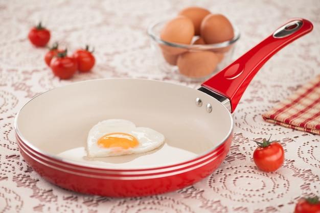 Panela com ovo frito e tomate em uma toalha de mesa branca