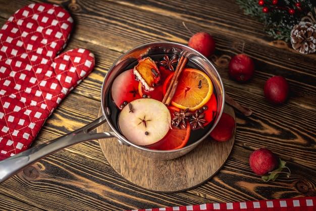 Panela com quentão quente perfumado picante em uma mesa de madeira rodeada de frutas e acessórios festivos. conceito de uma atmosfera acolhedora de férias, clima de ano novo e natal.