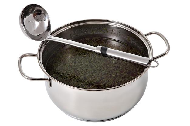 Panela de aço com sopa e concha de aço inoxidável, isolada no branco.