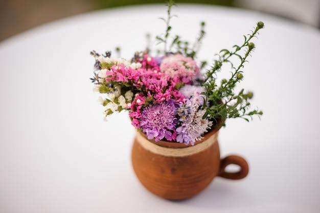Panela de barro com lindo buquê de flores