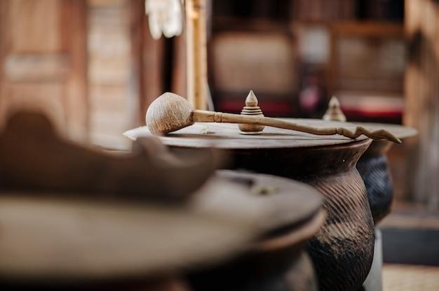 Panela de barro com tampa de madeira coberta com concha de água