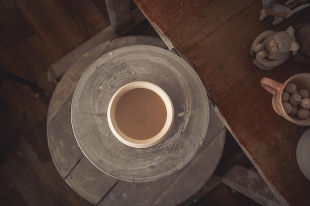 Panela de barro em close-up de uma roda de oleiro. copiar spase