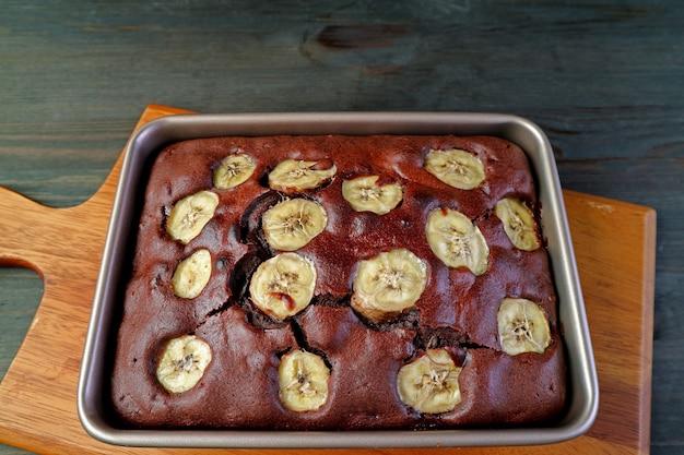 Panela de bolo de banana com chocolate caseiro fresco assado na tábua de pão de madeira