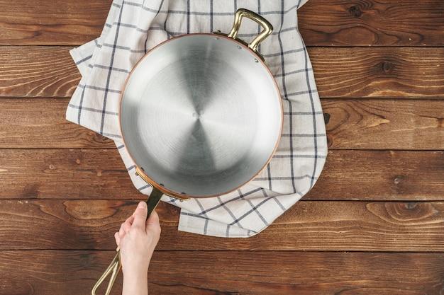 Panela de cobre brilhante na mão do cozinheiro na vista superior do plano de fundo de madeira