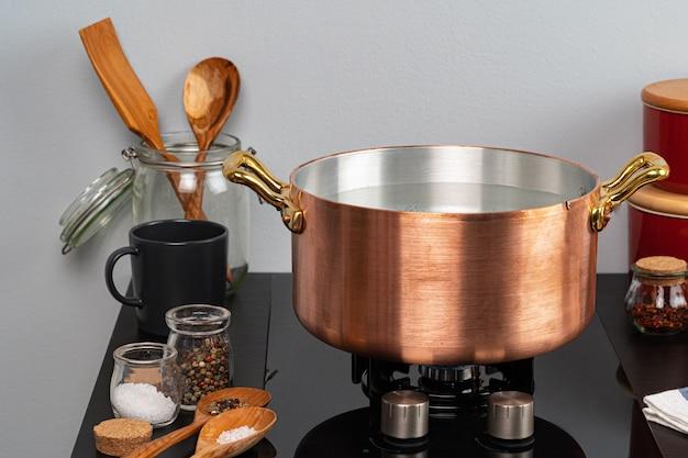 Panela de cobre com água a ferver em um fogão a gás close-up