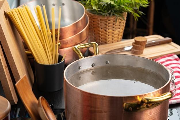 Panela de cobre com água a ferver em um fogão a gás