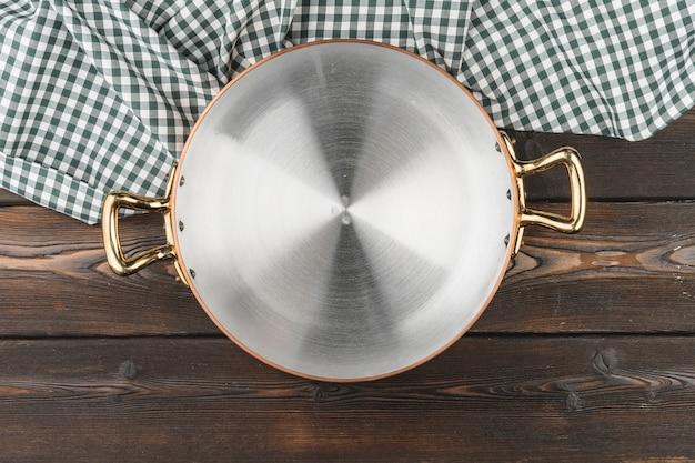 Panela de cobre com toalha de mesa chekered na mesa de madeira