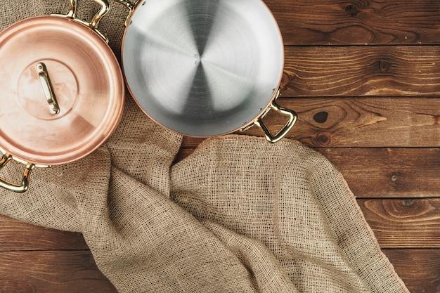Panela de cobre na mesa de madeira escura, vista superior