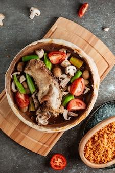 Panela de ensopado de borrego recheada com cogumelos frescos, batata, tomate e pimentão