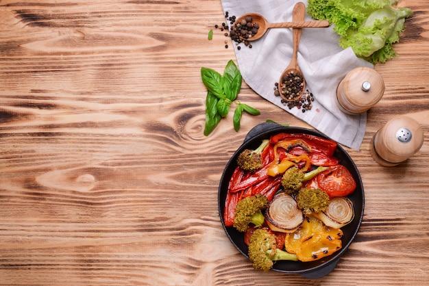 Panela de ferro fundido com legumes grelhados na mesa de madeira