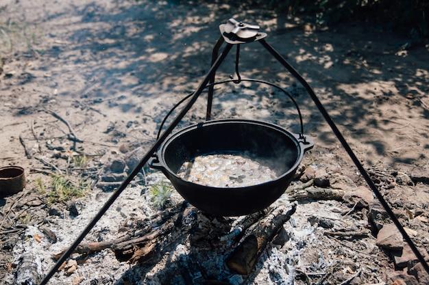 Panela de ferro fundido cozinha em fogo aberto em um acampamento