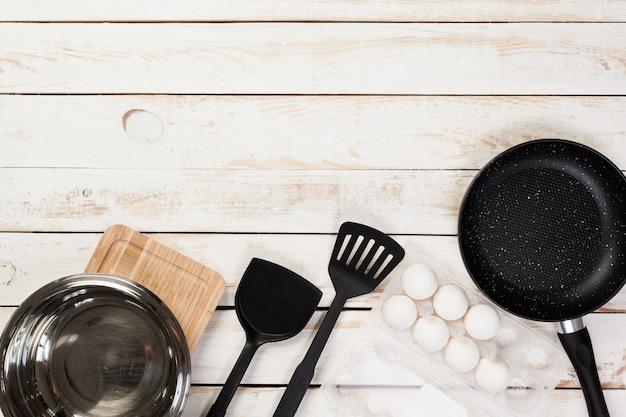 Panela de ferro fundido e outros utensílios de cozinha na mesa de madeira, vista superior