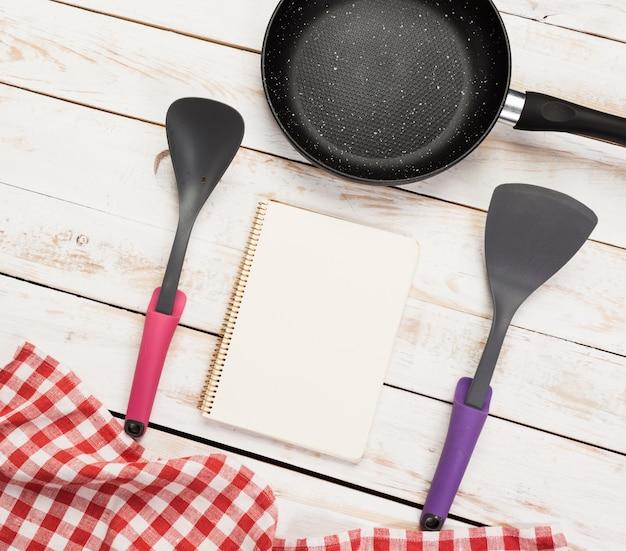 Panela de ferro fundido e outros utensílios de cozinha na mesa de madeira