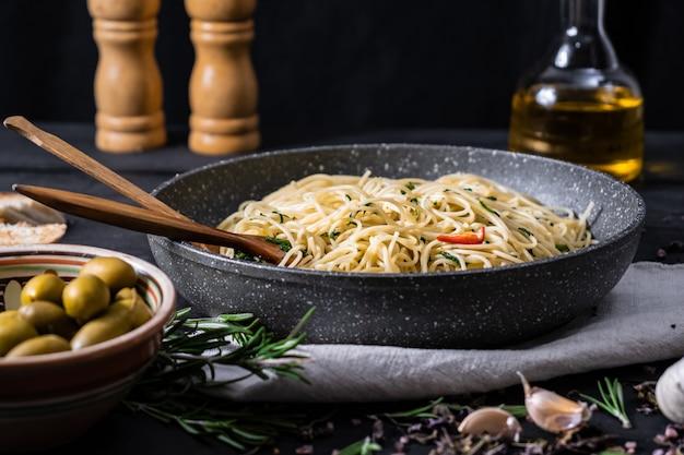 Panela de macarrão italiano cozido. refeição tradicional de espaguete com legumes e azeitonas na superfície rústica preta